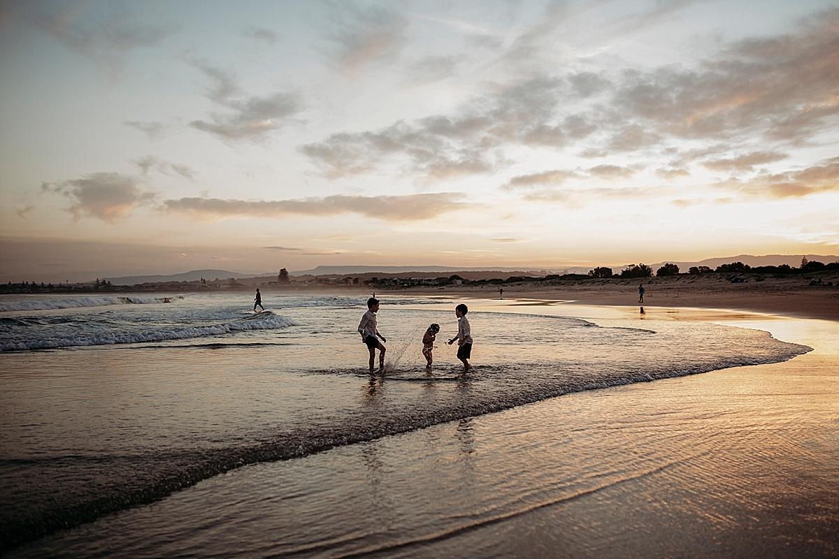 siblings at beach at sunset