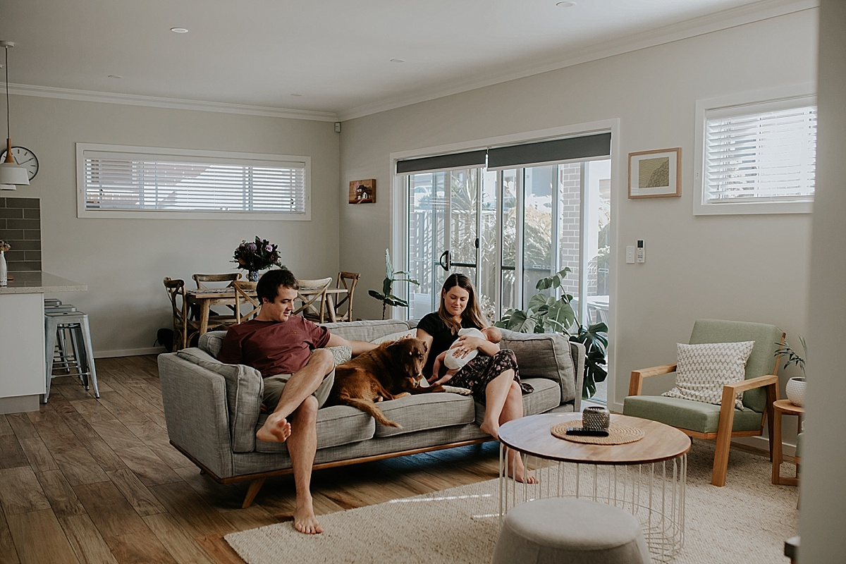 family on lounge together with dog