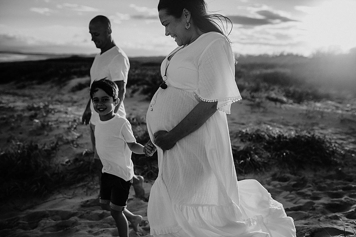 black and white image of family of 3 holding hands walking down the beach, pregnant baby.