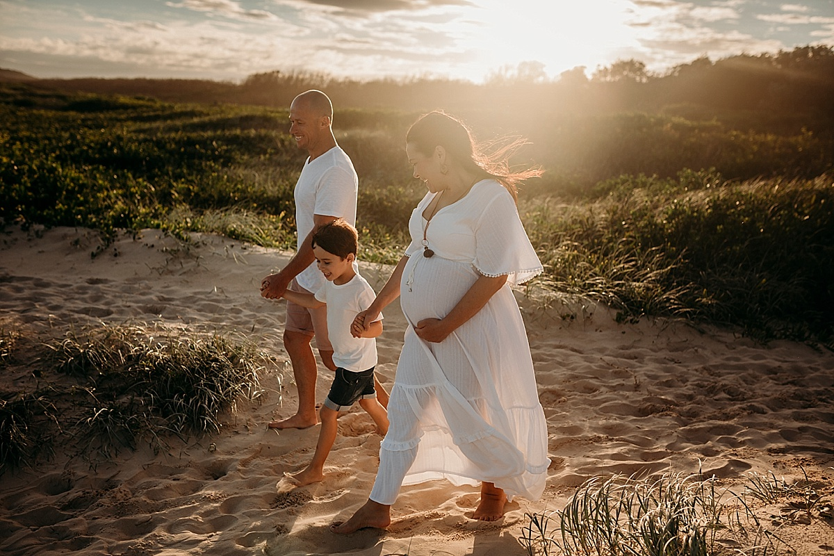 Pregnant mum, son and husband walking down to the beach at sunset