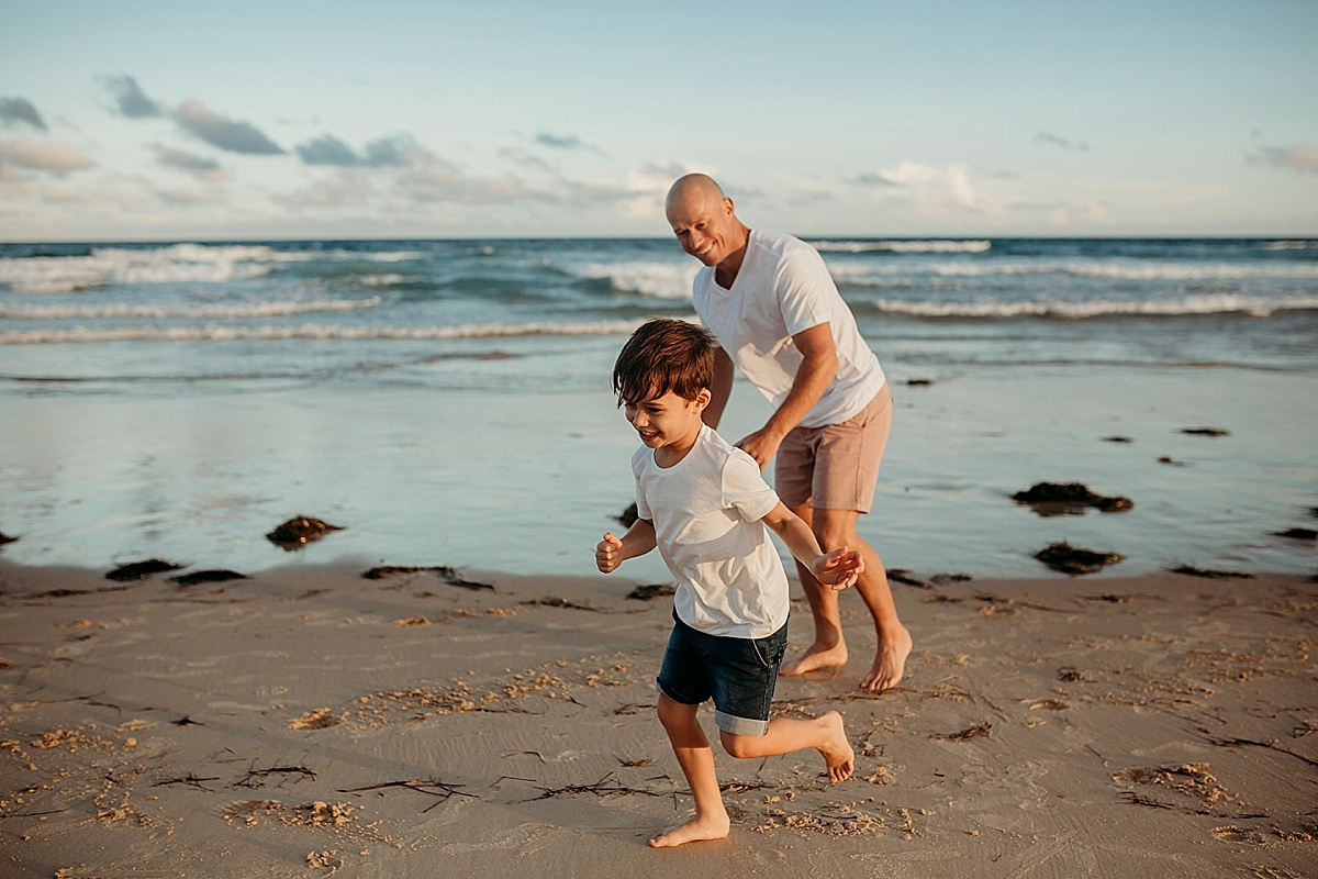 father and son running along port kembla beach