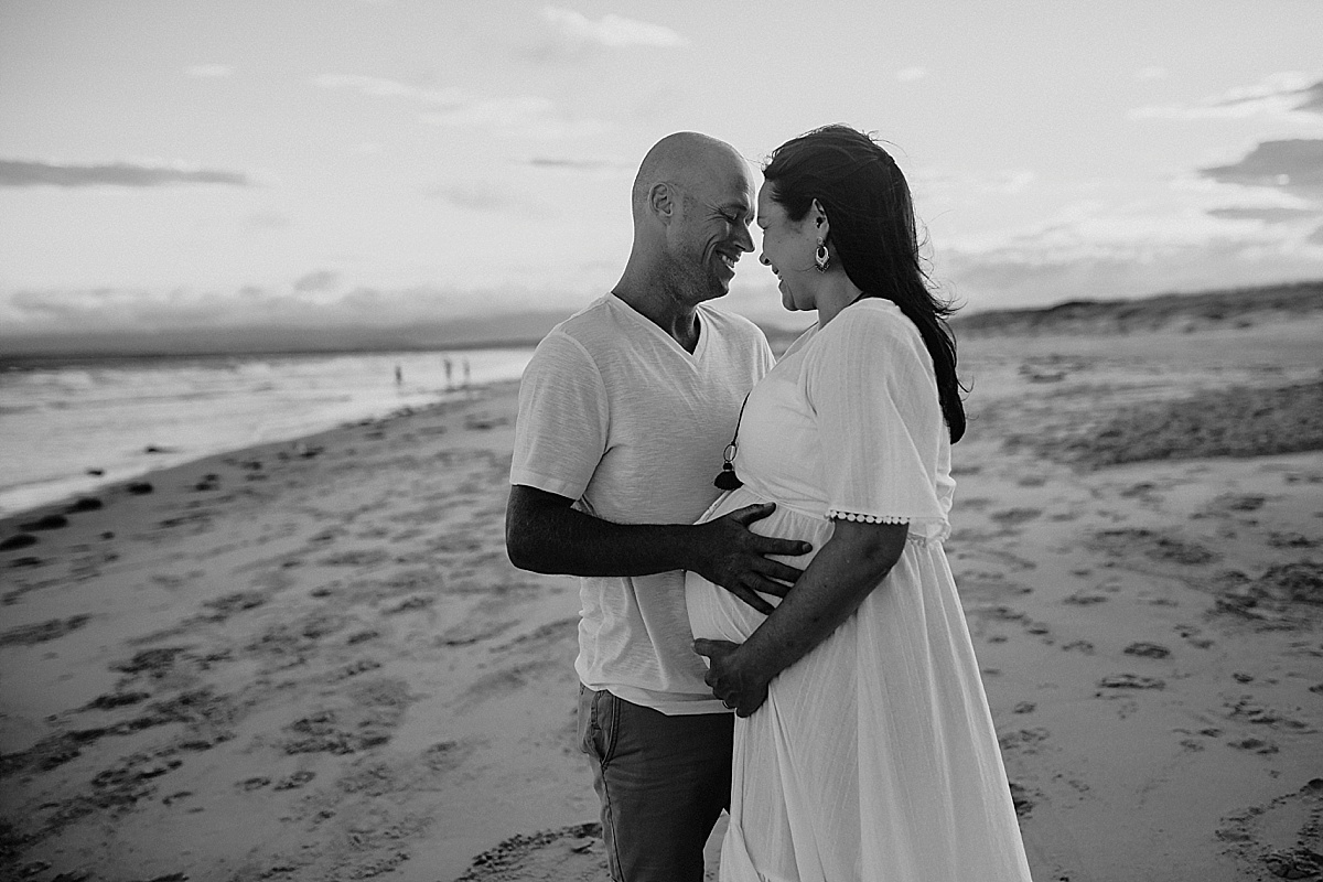 husband gently cuddling pregnant wife at wollongong maternity session