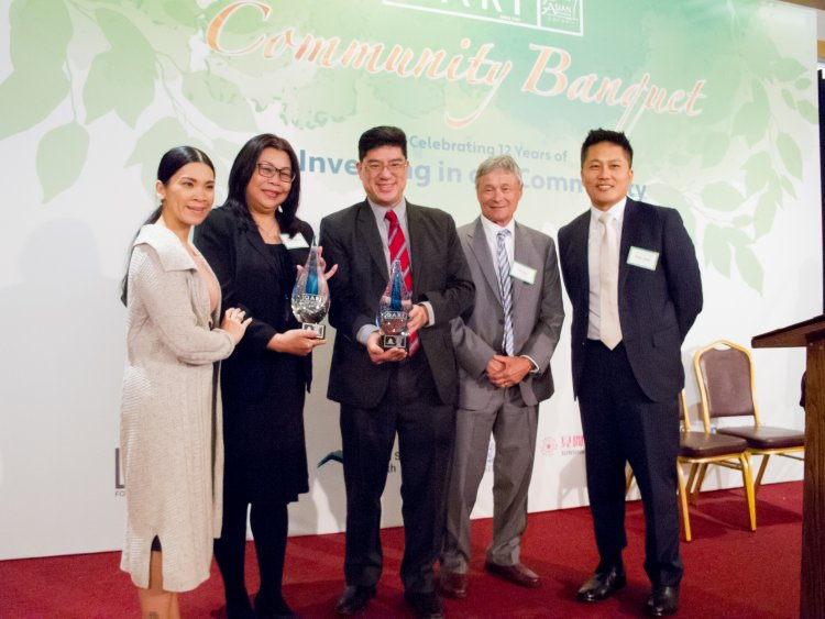 State Rep. Tackey Chan (center) presents the Visionary Award to State Street assistant vice president of global diversity and inclusion Tamie Phan (first from left), and State Street Asian Professionals Alliance coordinator Sandy Wong-Ng (second from left) at the 12th annual QARI Community Banquet on May 17 at the China Pearl. Also pictured are QARI board chairman Paul Shaw (second from right), and QARI president and CEO Philip Chong (first from right). (Image courtesy of Felix Poon.)