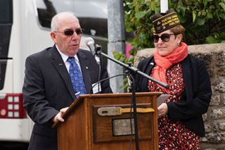 Dr. John R. Dabrowski, Colonel, US Army Retired, delivers an address at the memorial for Chaplain Maternowski in Guetteville, France on June 8, 2019. With him is retired Army lieutenant colonel Kelly Carrigg who acted as translator during the speech.