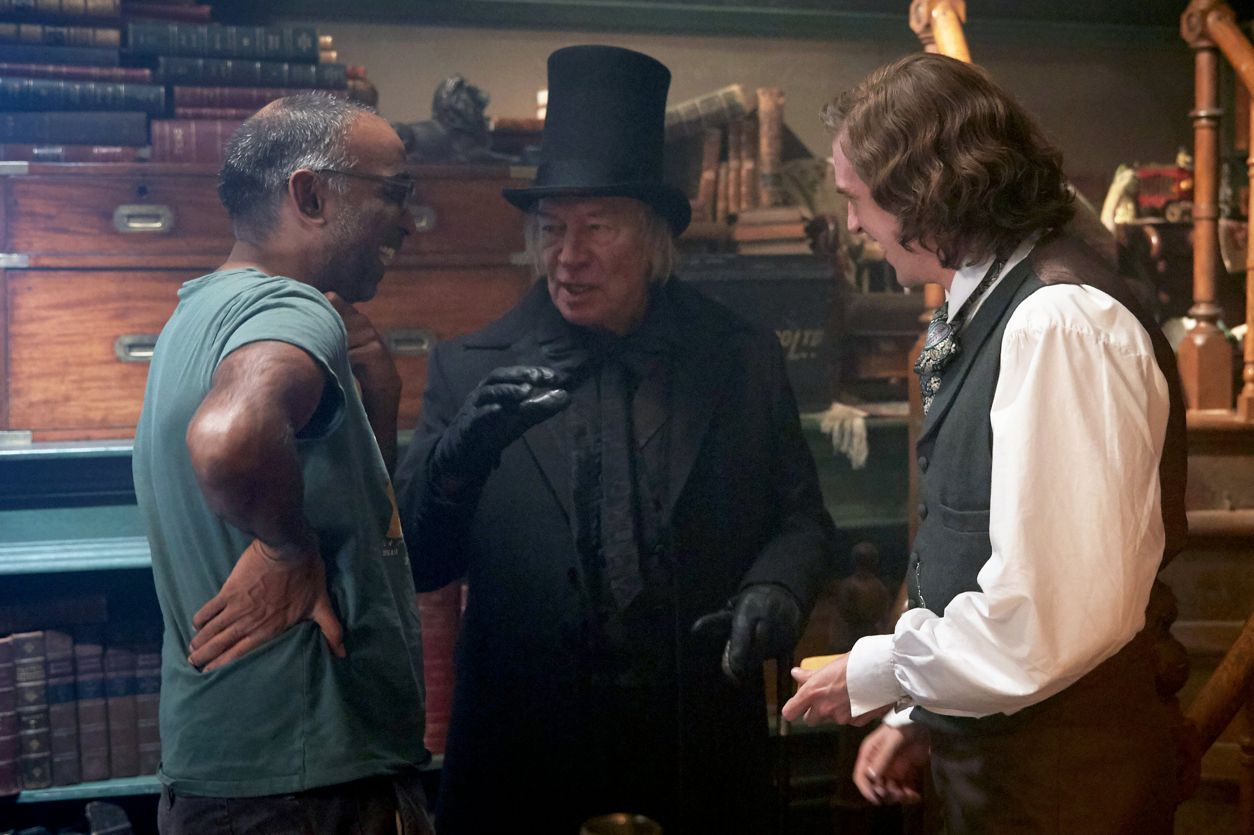 Director Nalluri talks over a scene with Scrooge (Plummer) and Dickens (Stevens)