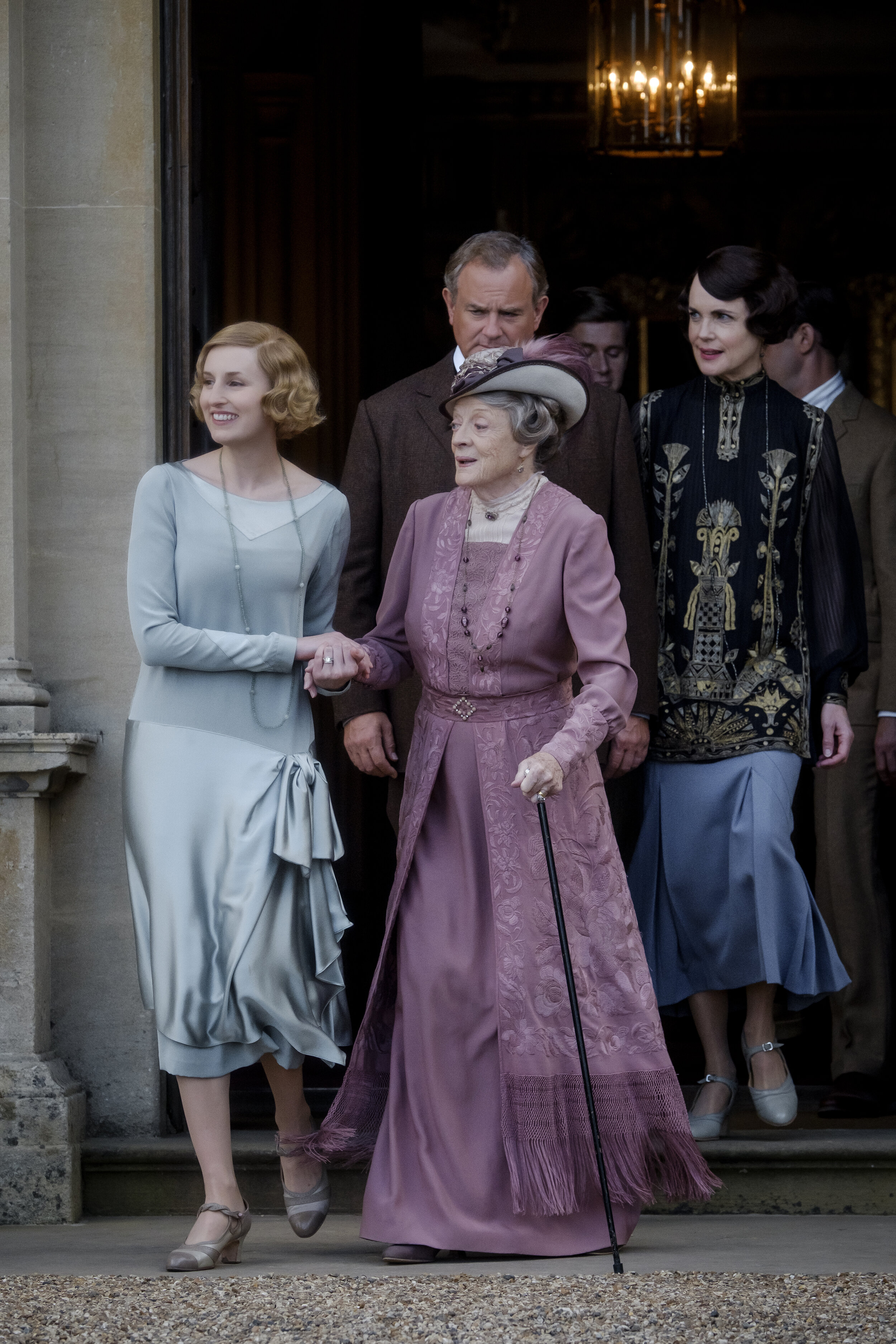 Dame Maggie Smith as Violet Crawley being led to greet royalty.