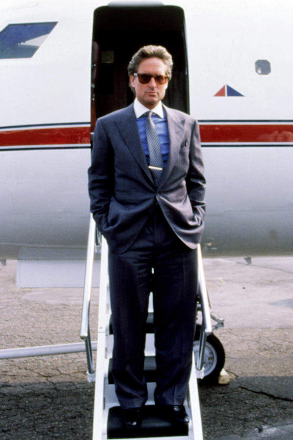 Sporting another blue shirt with a white contrast collar shirt this time under a grey single-breasted suit, Gekko accessorises with a tie, silver tie bar, pocket square and pair of Ray-Ban wayfarer sunglasses. Photograph by 20th Century Fox Film Corp/ Everett/Alamy.
