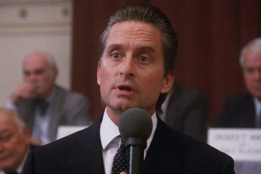 """During his iconic """"greed is good"""" speech, Gekko wears a grey [actually navy! -AF] double-breasted suit with a white double cuff shirt and spotted tie, finished with a simple white pocket square."""