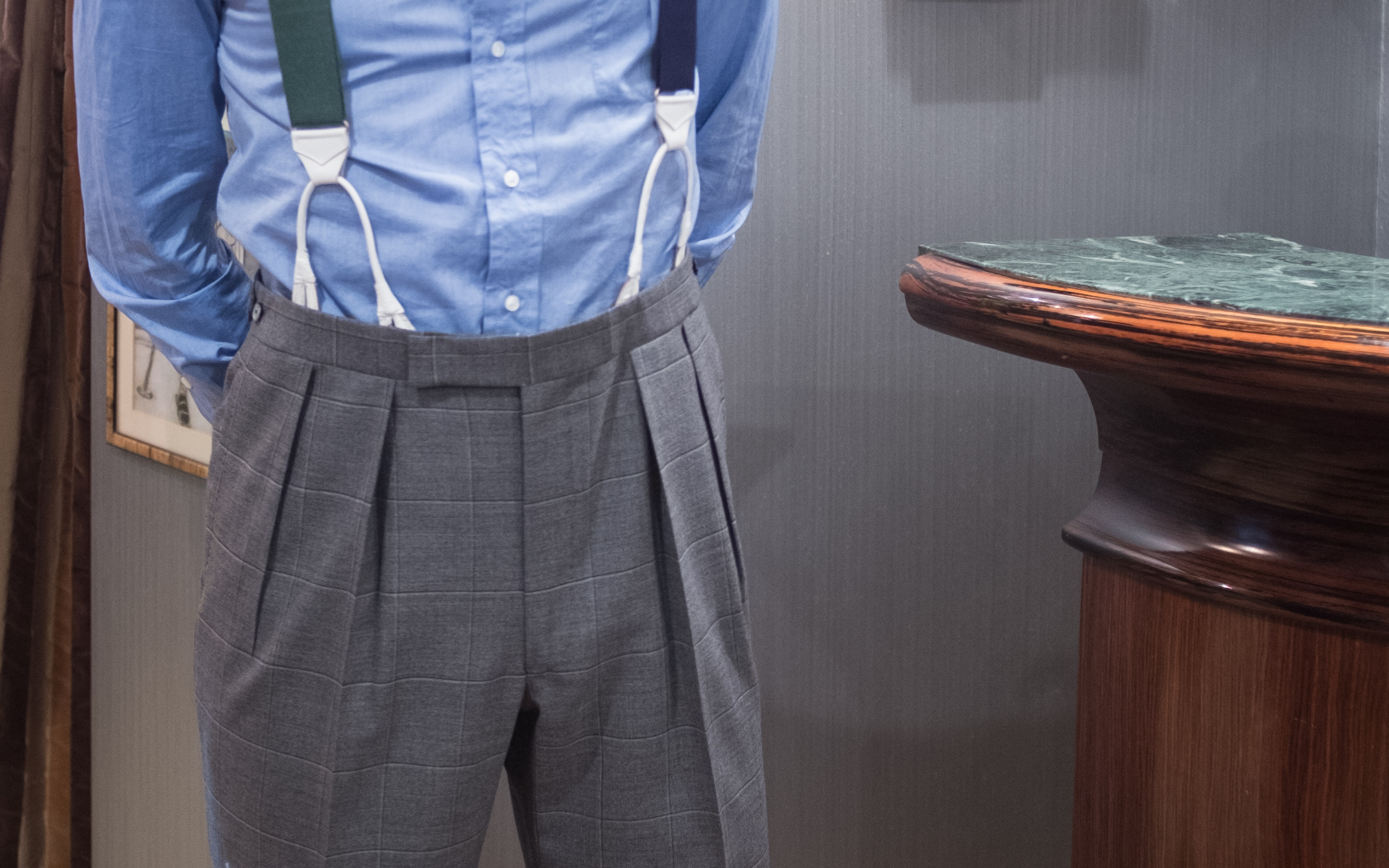 """With pleated trousers, the front """"bracer buttons"""" are generally sewn at the first pleat, to help the trouser line hang properly."""
