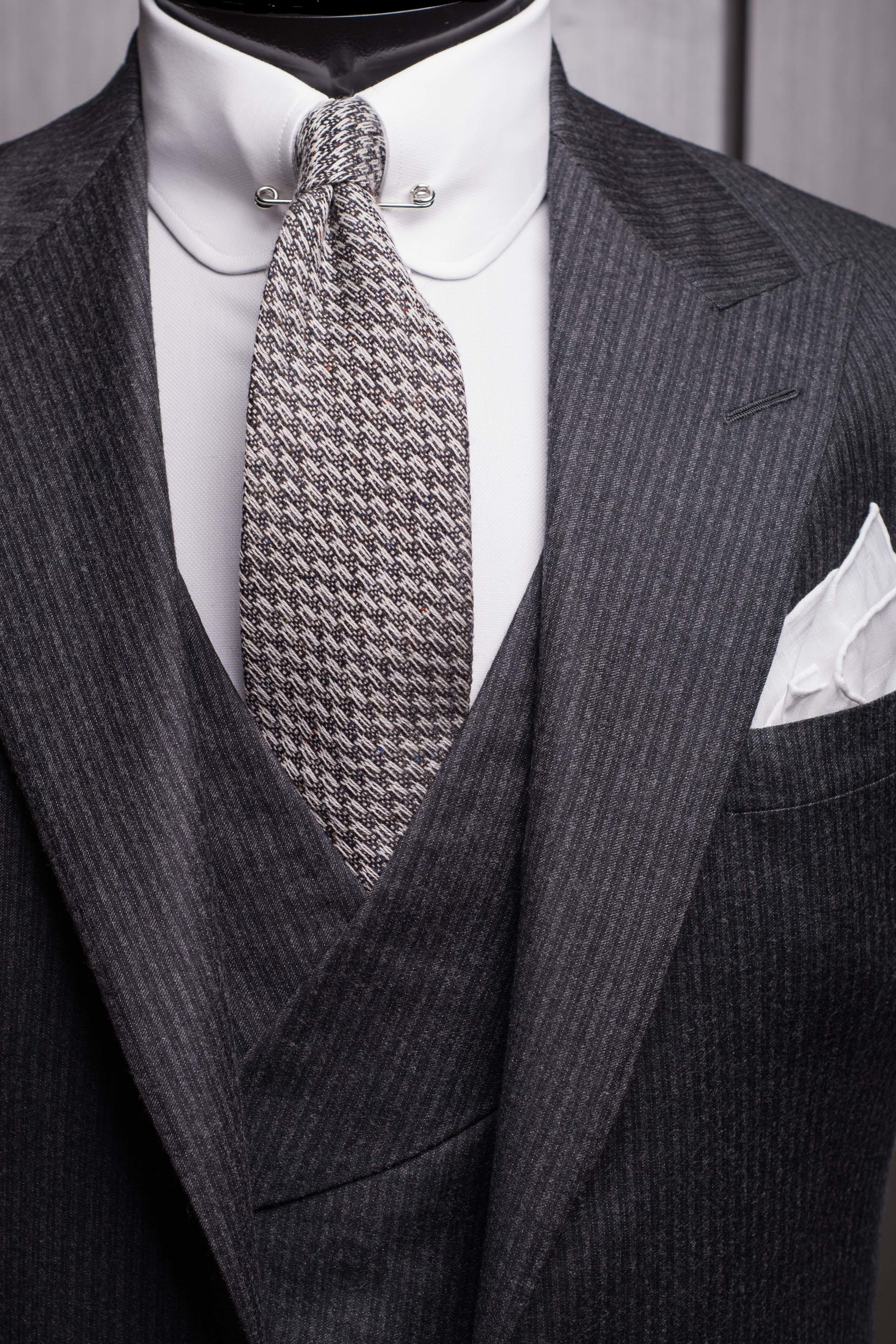 A heavily textured wool tie plays an unexpected but effective role in this highly formal monochromatic presentation.