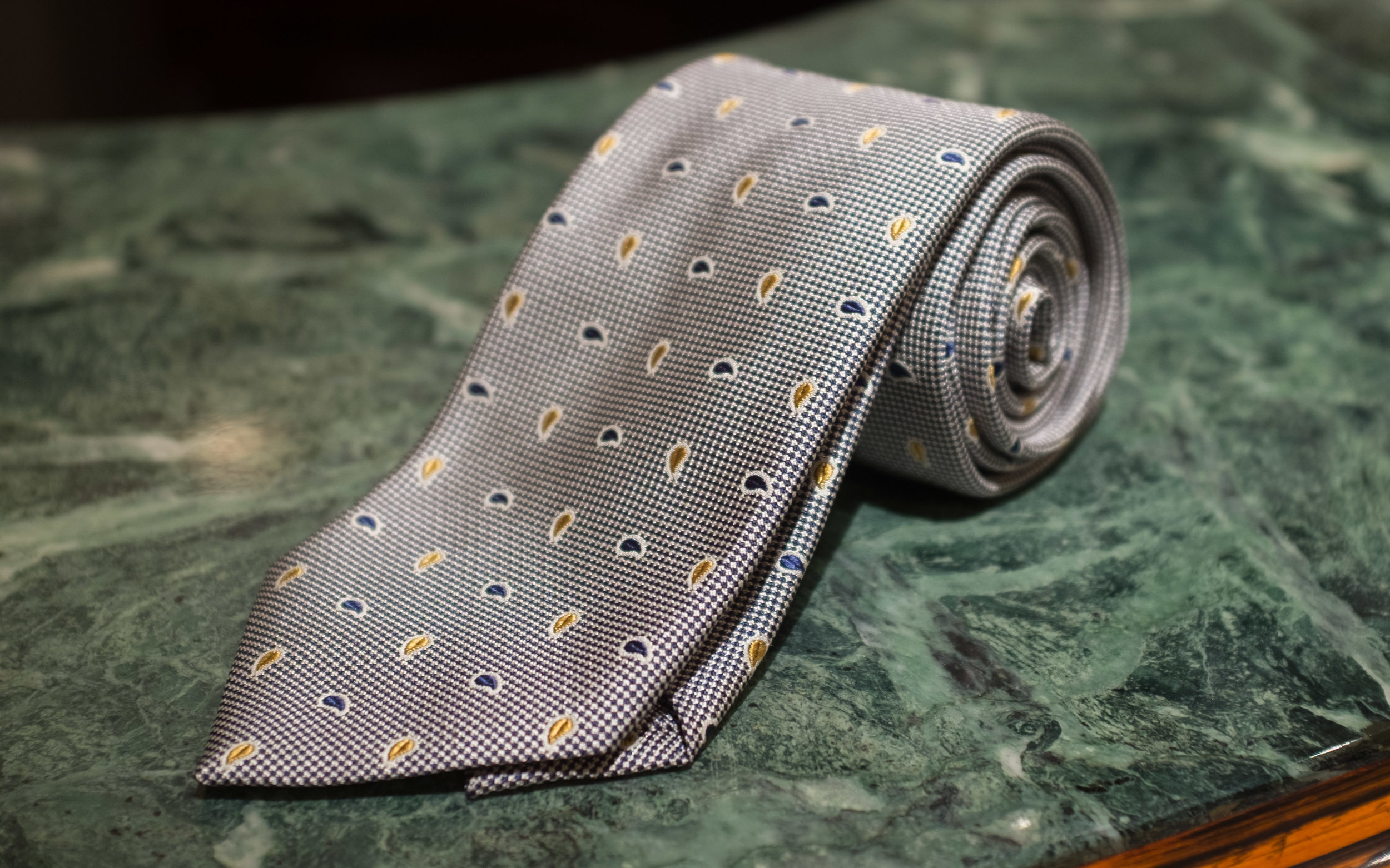 Macclesfield Woven Silk Paisley  - The paisley elements here have been abstracted to their geometric essence and reduced in scale to be subtle decorations on a woven black and silver field, making this is a very dressy tie intended to be worn with suits.