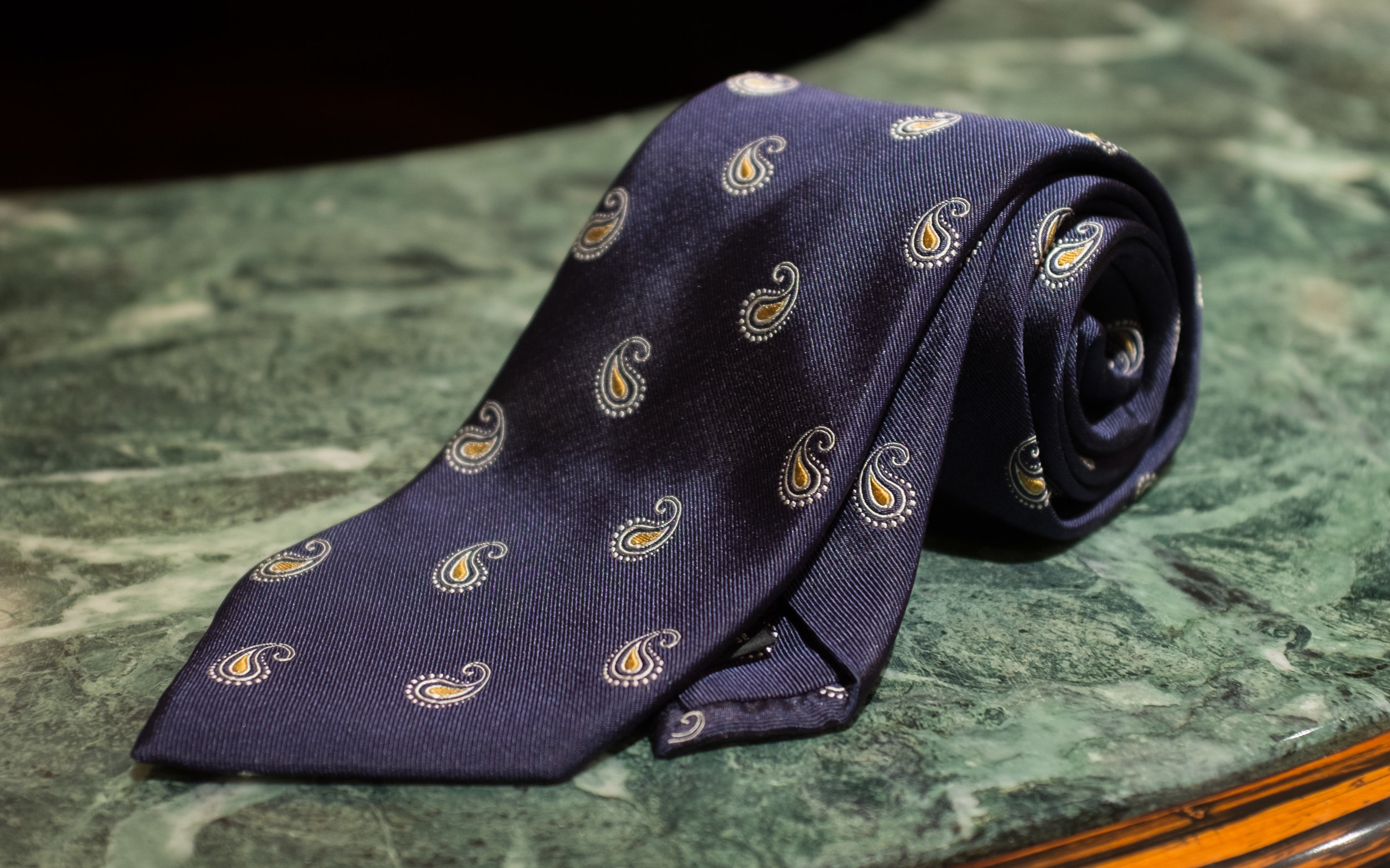 Woven Silk Spaced Paisley  - The modestly sized yet prominent paisley motif on a navy field gives this tie an almost crested effect, appropriate with either a suit or blazer.