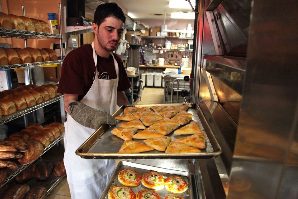 Tayara retrieves a cooling sheet holding spinach fatayer from an oven.
