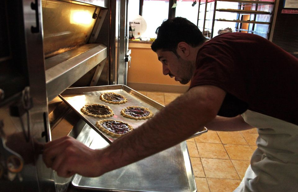 Molhem Tayara retrieves a cooking sheet holding zatar, a Syrian baked good, from the oven at the Victorian Bakery. Tayara, a refugee from Syria, has been baking goods every Saturday morning to help support his family.