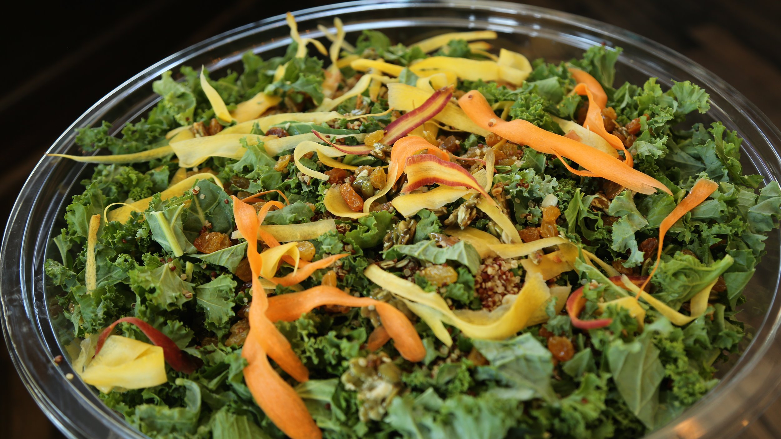 Kale quinoa salad with carrot ribbons, golden raisins, pepita sesame clusters