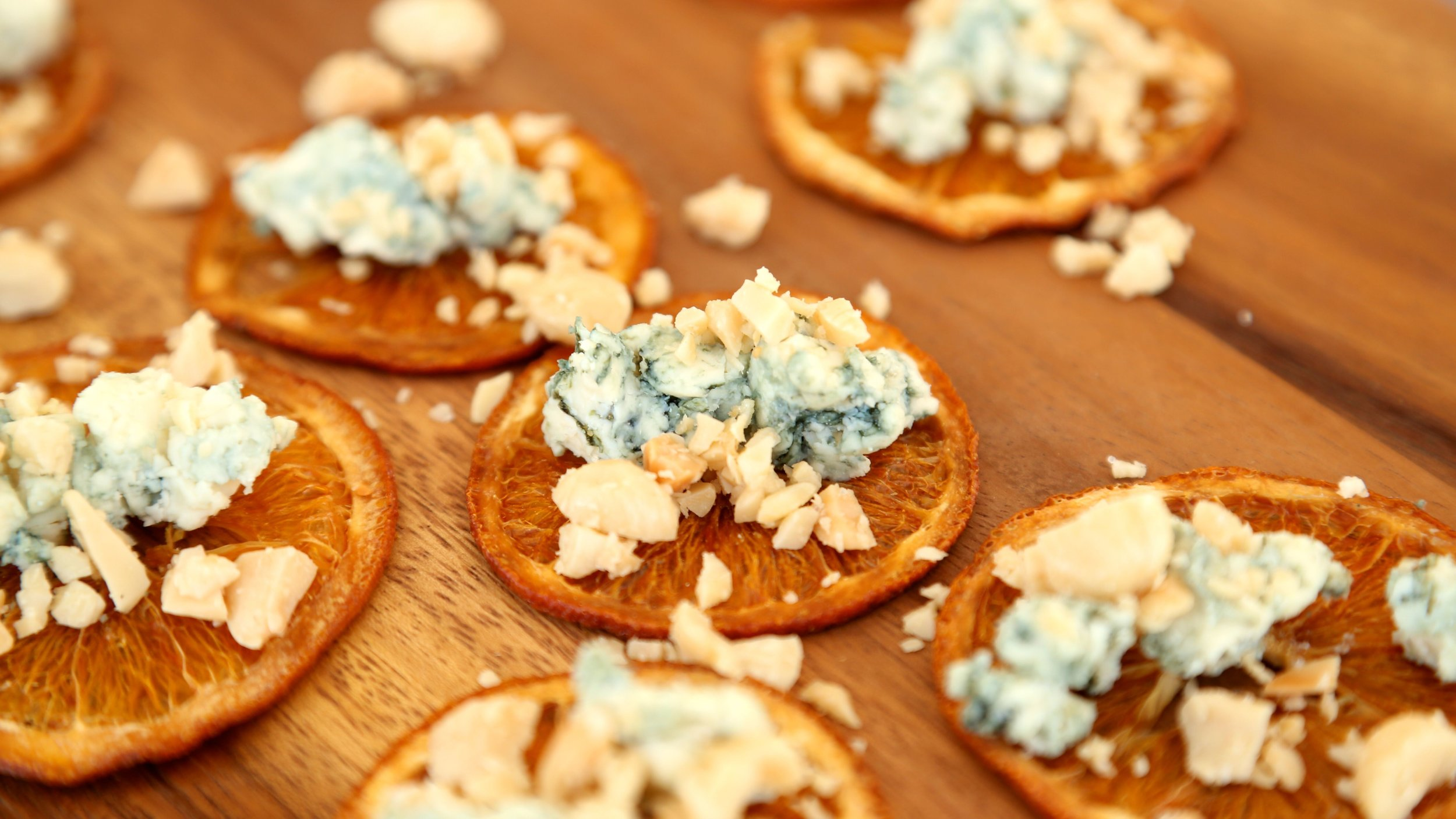 Blue cheese and marcona almond bites on orange crisps