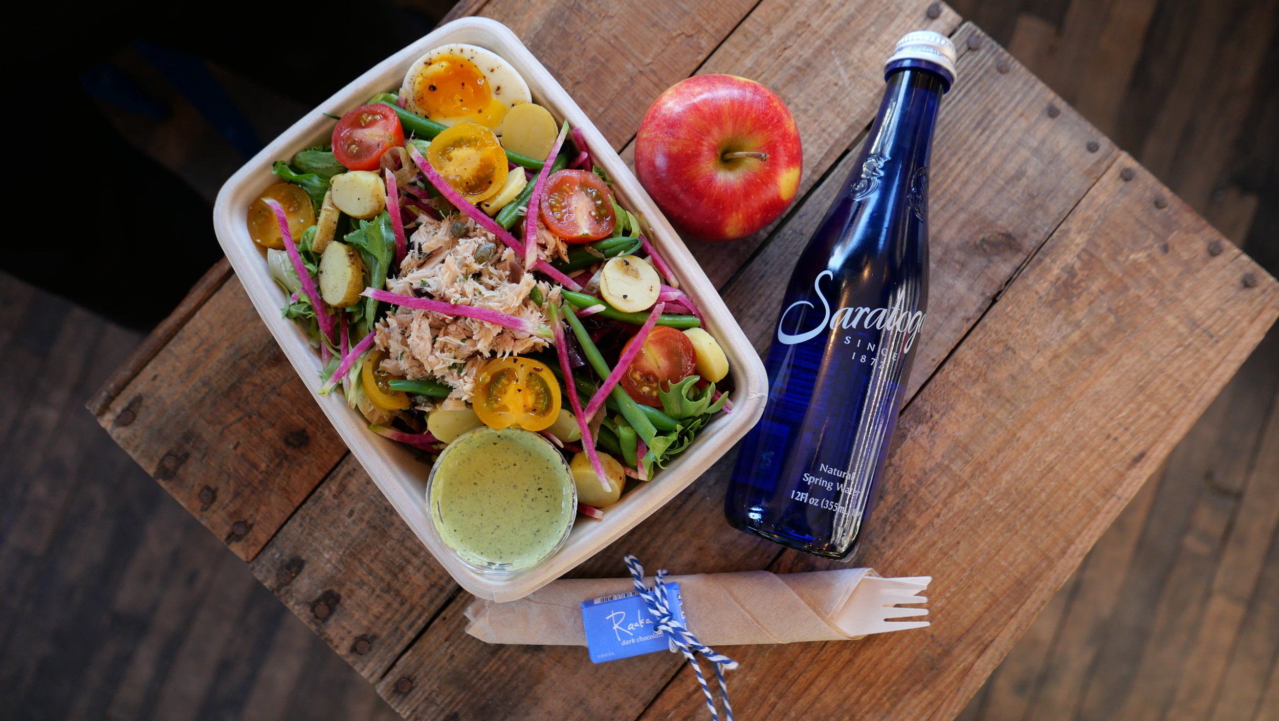 The lunch box shown with niçoise salad
