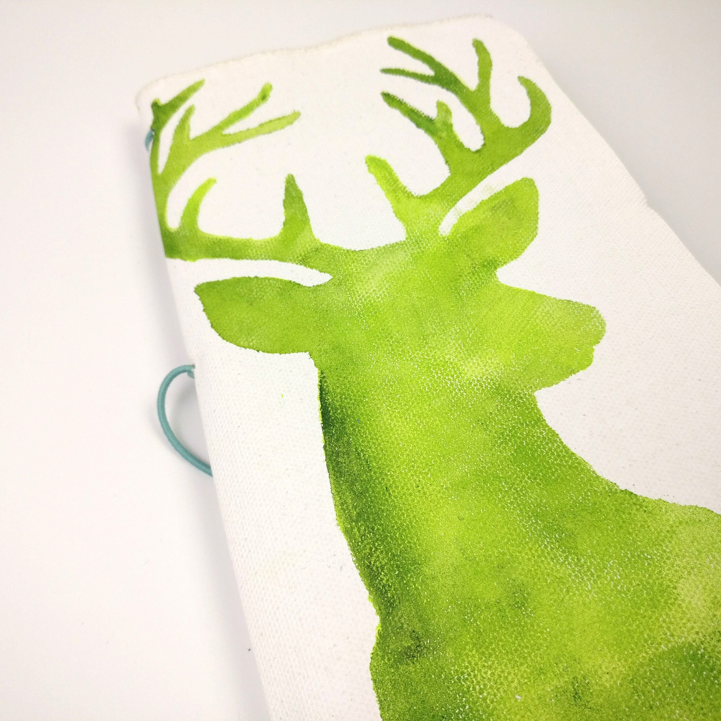 Make Your Own Custom Travellers Notebook Cover I'm sharing how I have made my custom cover for my Travellers Notebook Size Junk Journal for my December Daily for 2017. I am determined to complete December Daily this year! I'm working with Judit Pfaff Daley's new Deer with Antlers Stencil to create a a green watercolor effect on my canvas cover.