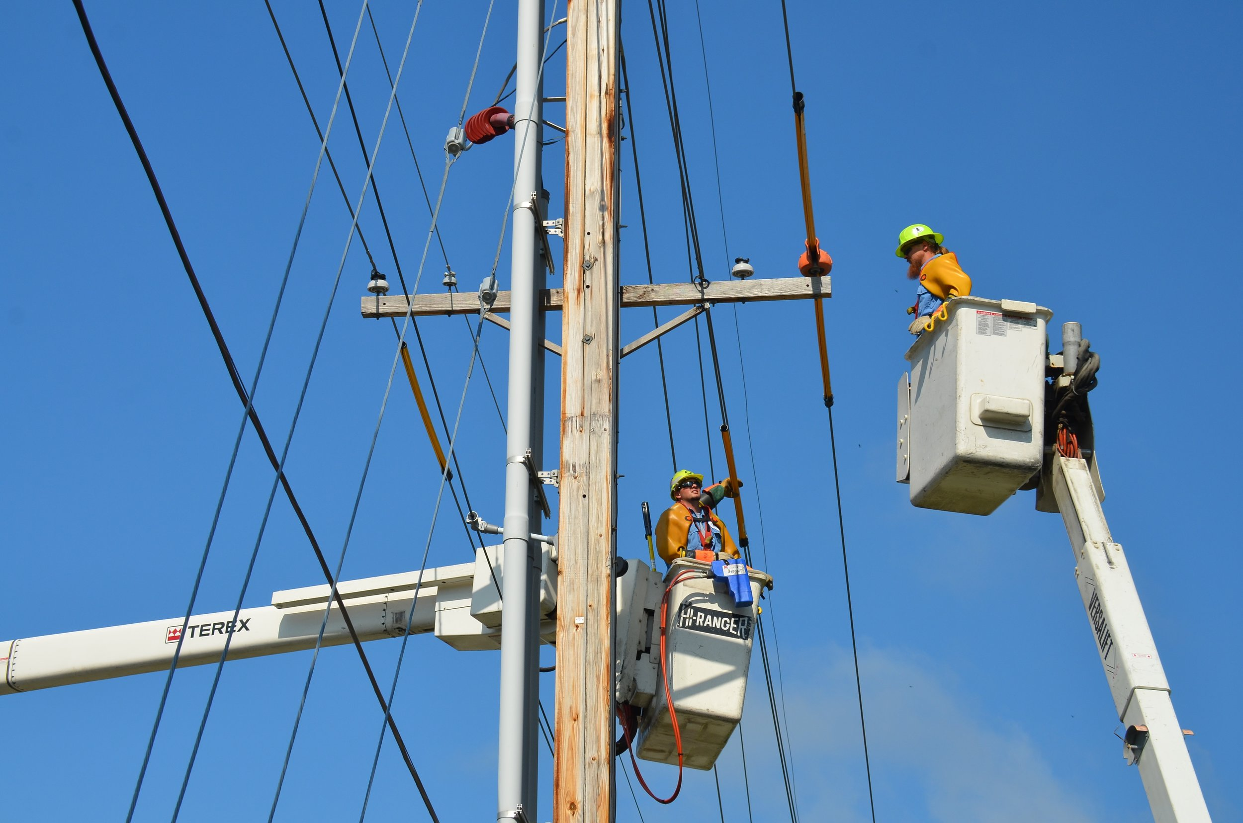 utility linemen workers in cherry picker