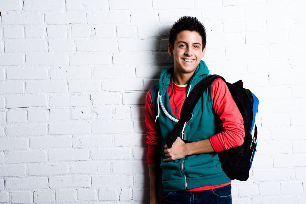 Smiling student standing in a school hallway, looking at the camera.