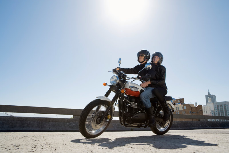 Two people riding a motorcycle, with a city in the background.