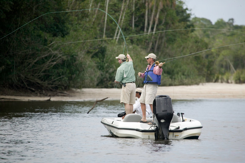 Two men fishing on a small speed boat.