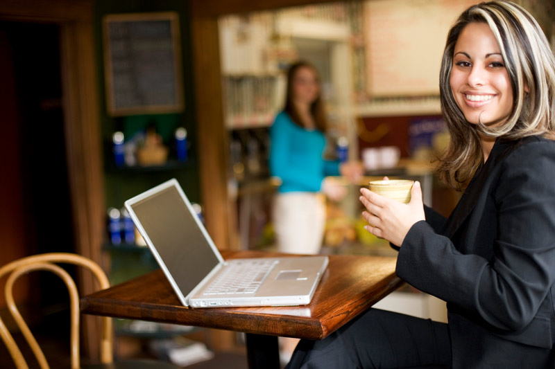 A smiling business woman, drinking coffee in front of her laptop at a coffee shop.