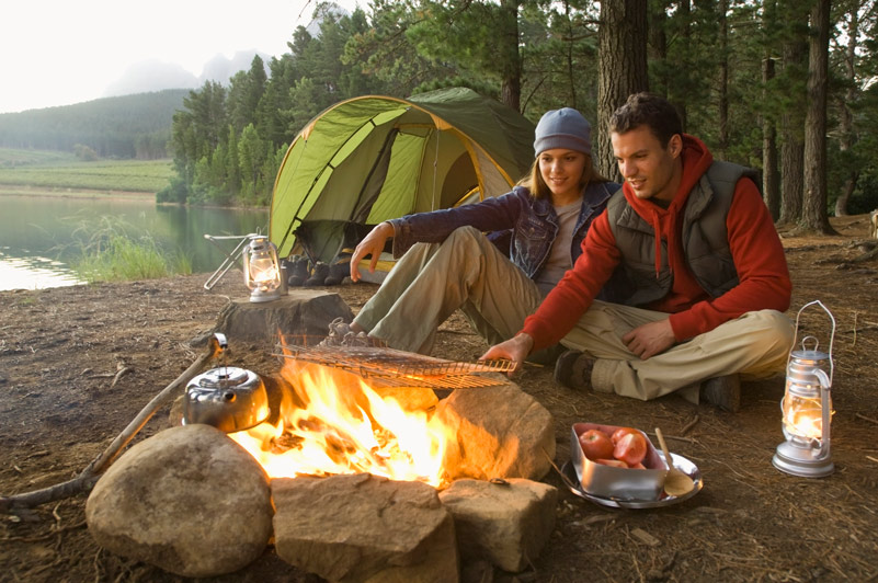 A man and a woman camping; cooking over a fire in the foreground, with a tent and gear behind them.