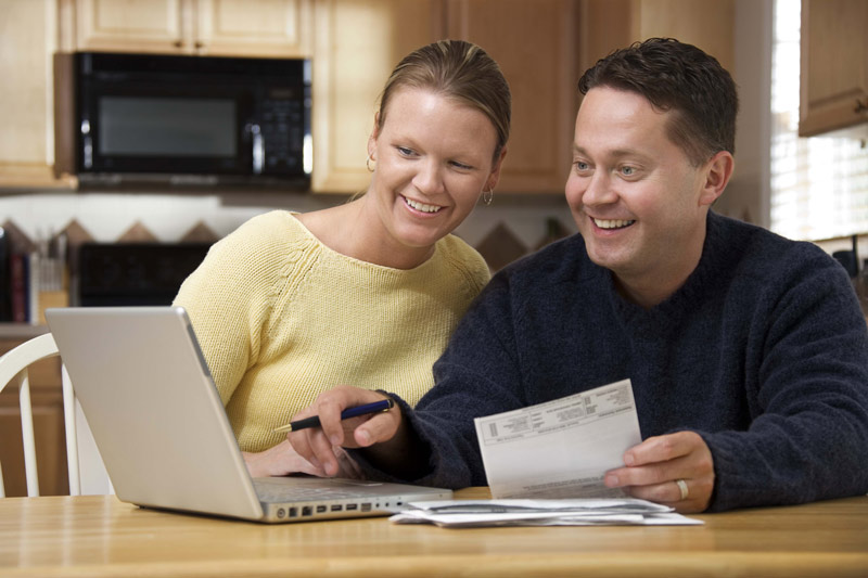 A married couple happily looking through their online bank statement on their computer.