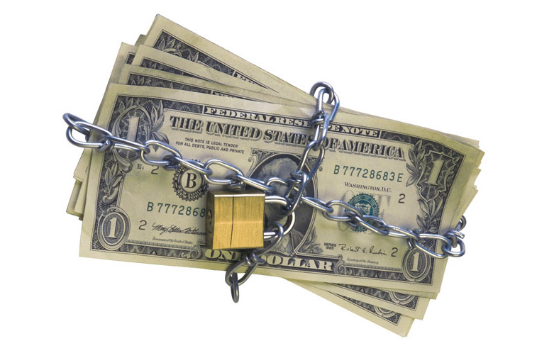 A stack a cash, with a chain and lock wrapped around it.