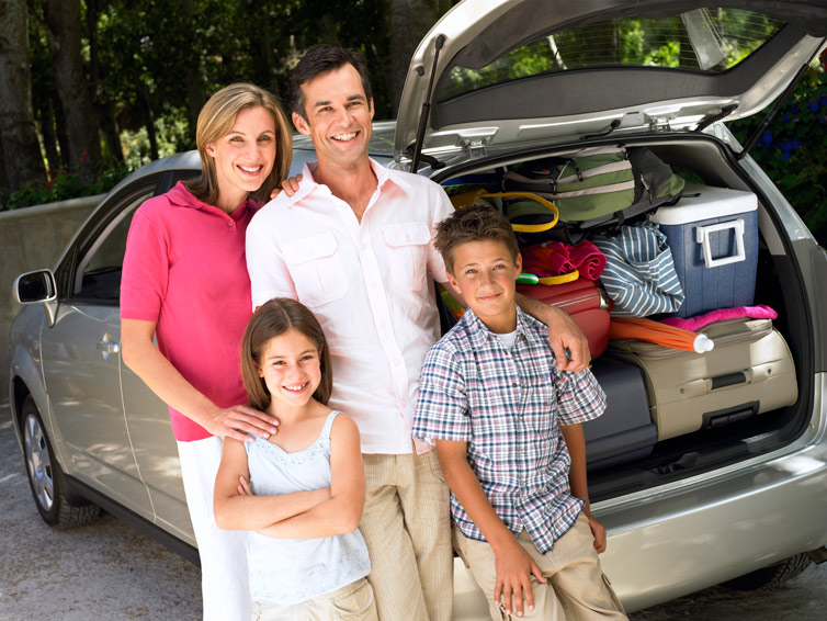 A family of four, standing in front of a mini van.