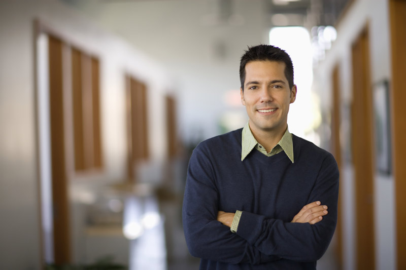 Smiling man standing in a hallway, arms crossed.