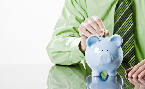 Piggy bank, facing the camera, with a hang putting a coin into it.
