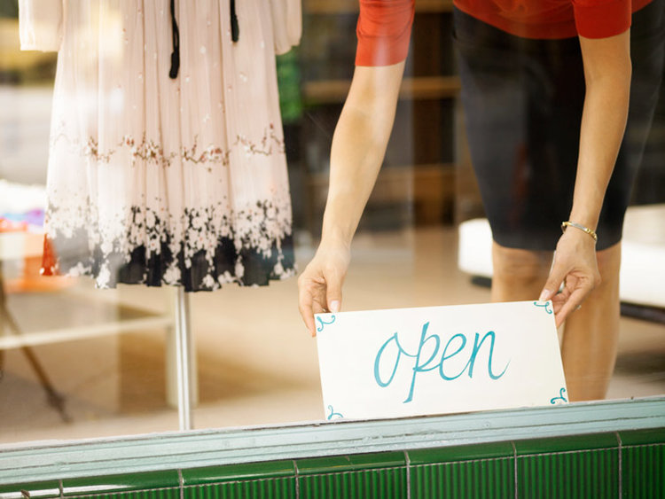 "Business owner putting an ""open"" sign in her shop front window."