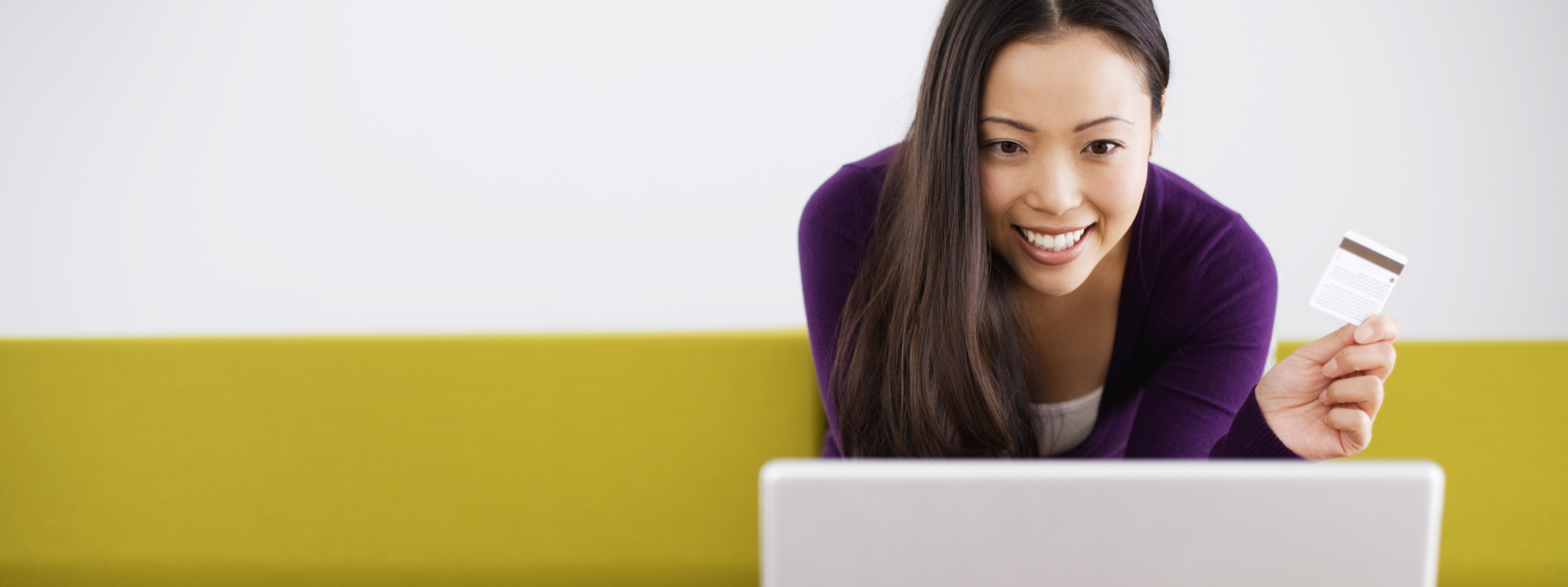 A smiling woman holding her credit card and looking at her laptop