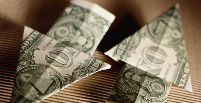 Two one dollar bills folded into arrow shapes