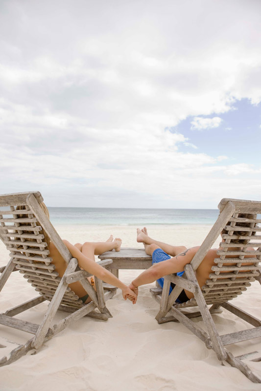 Young couple holding hands while relaxing in chairs on the beach.