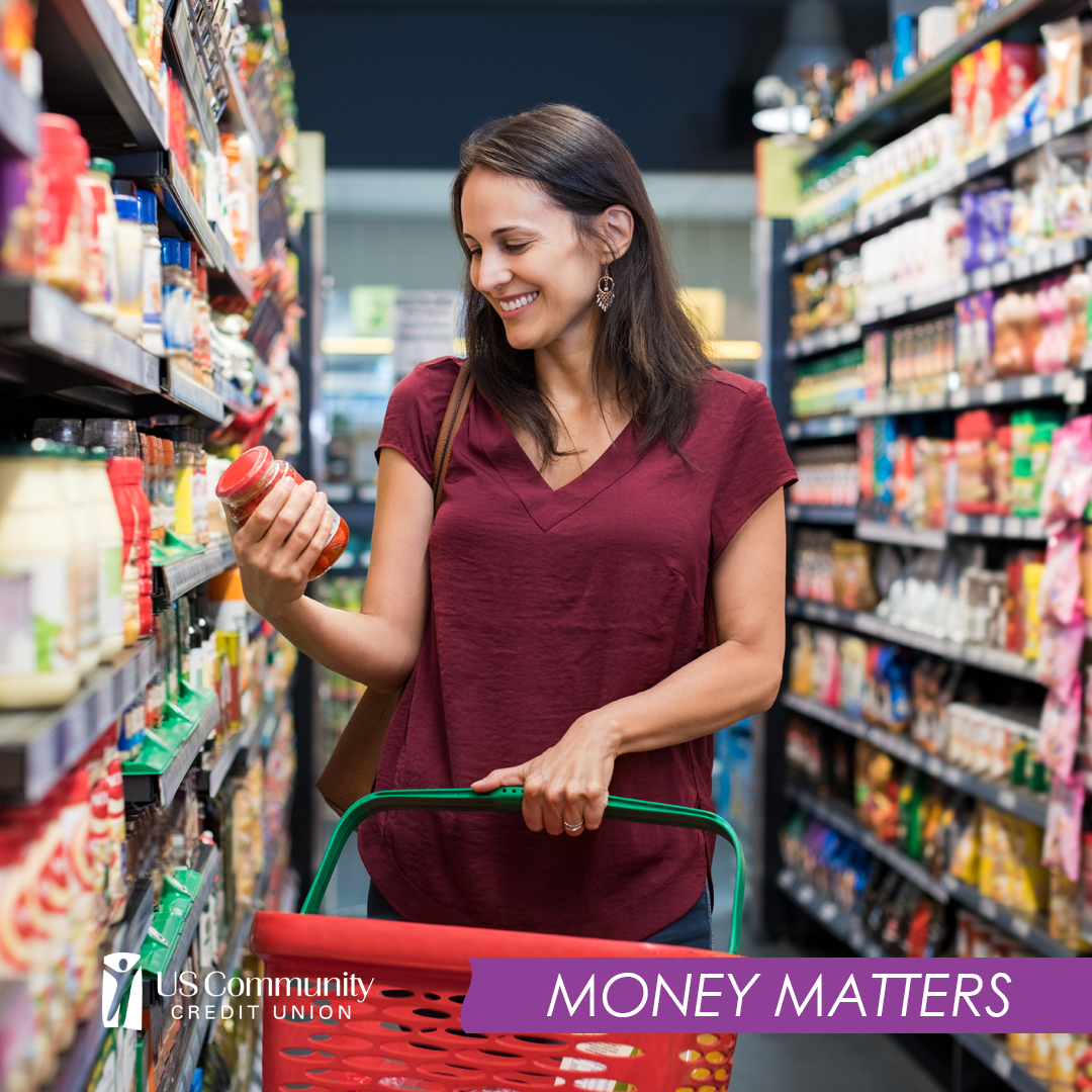 Woman holding food item in grocery store while holding a basket.