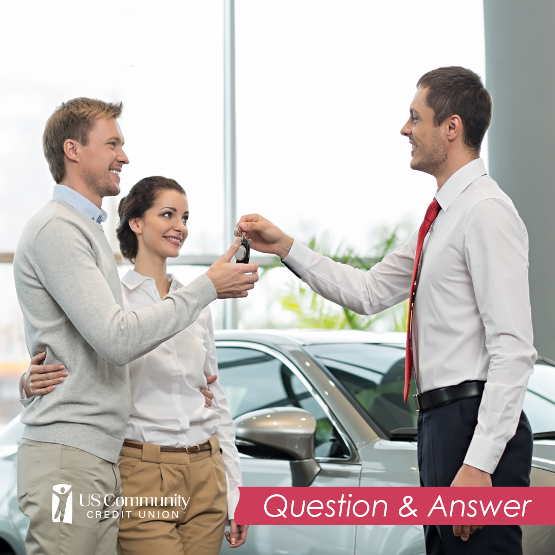 A couple getting the keys to a new car from a car salesman.