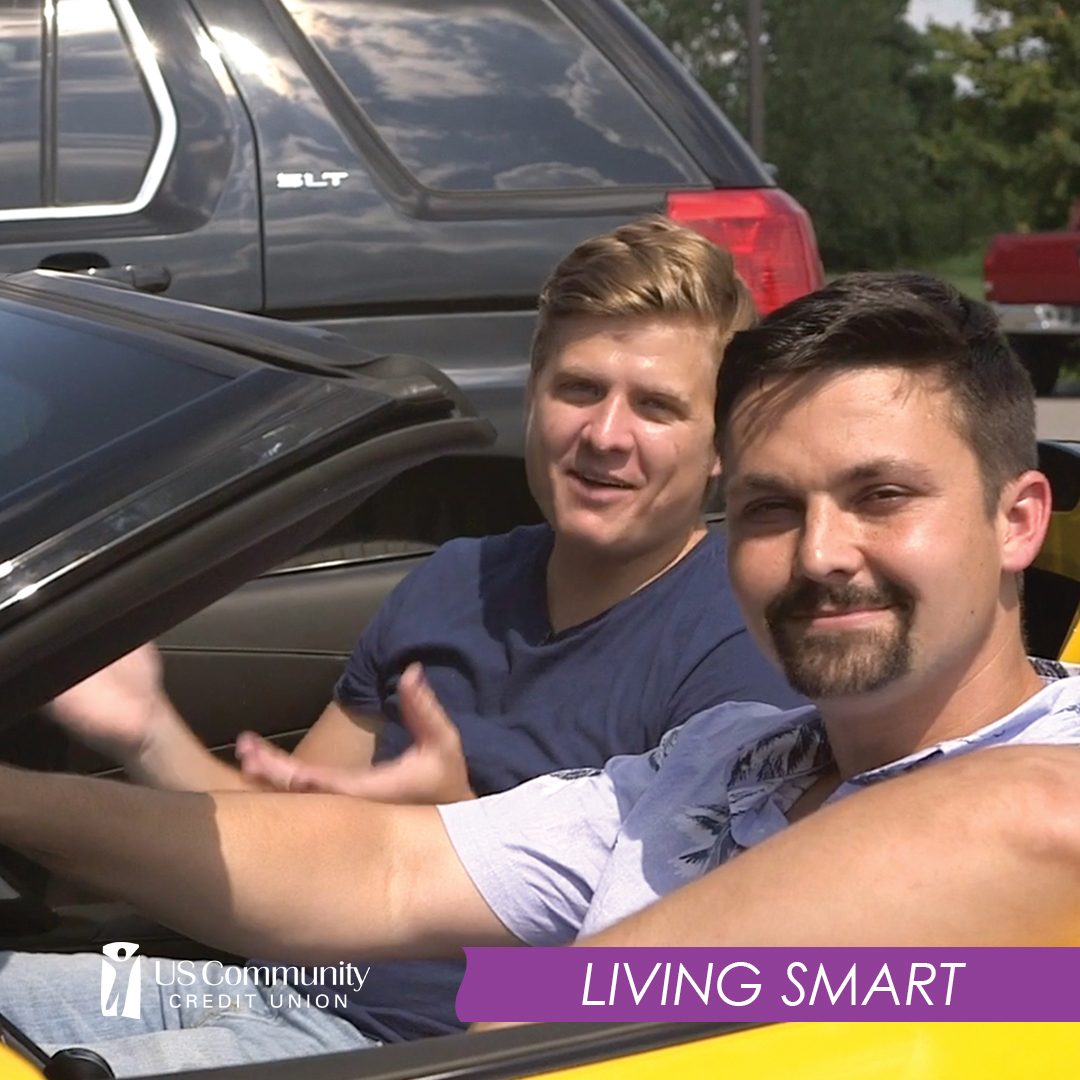 Two men sitting in a car at an auto dealership.