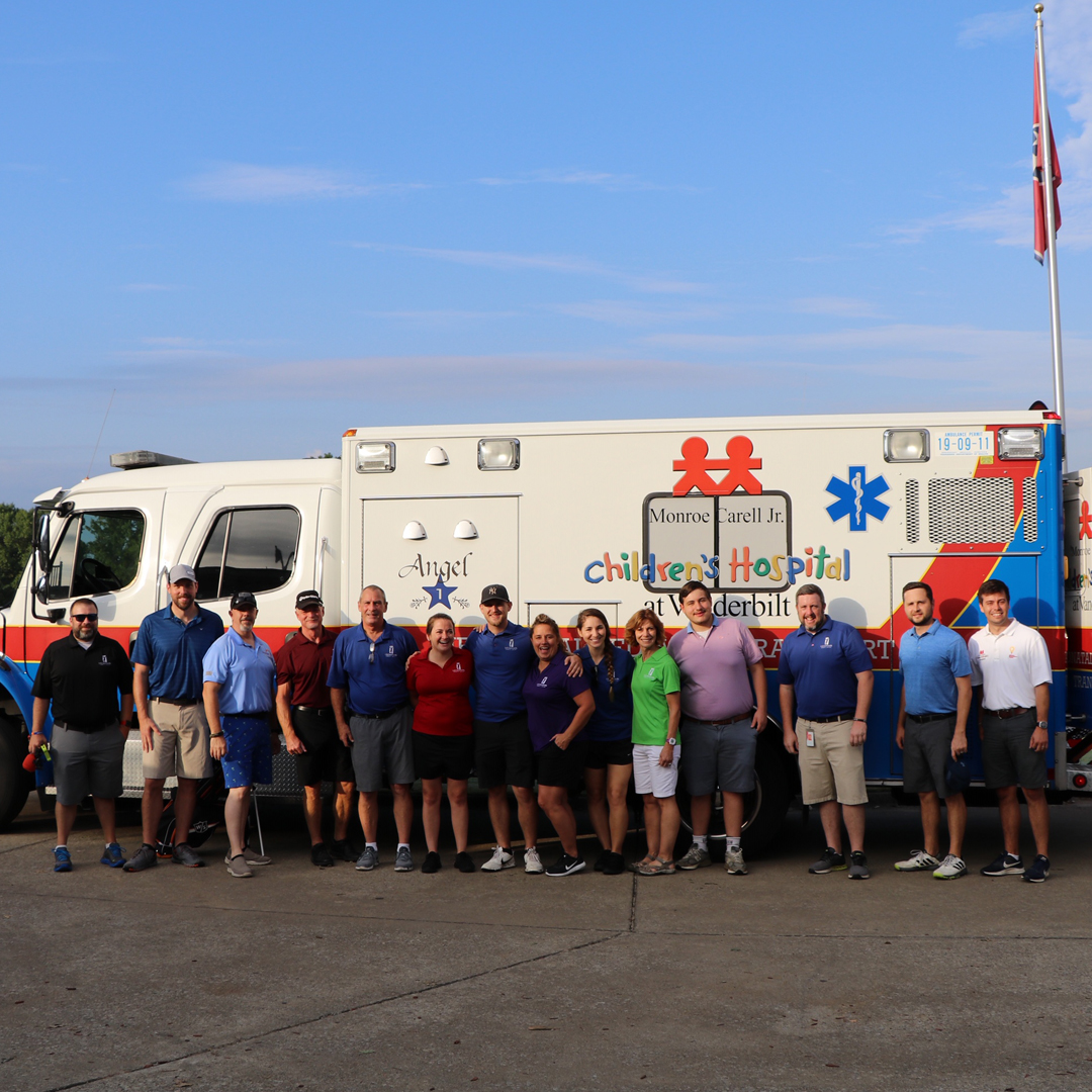 A group of people standing in front of a Vanderbilt Children's Hospital ambulance.