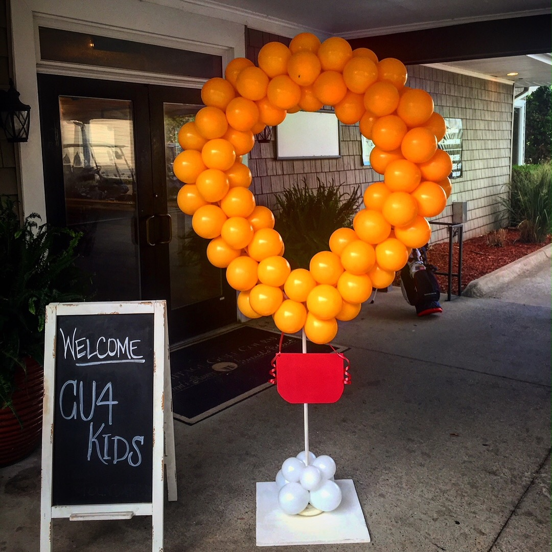 """A ring of balloons next to a sign reading """"Welcome CU4 Kids"""""""