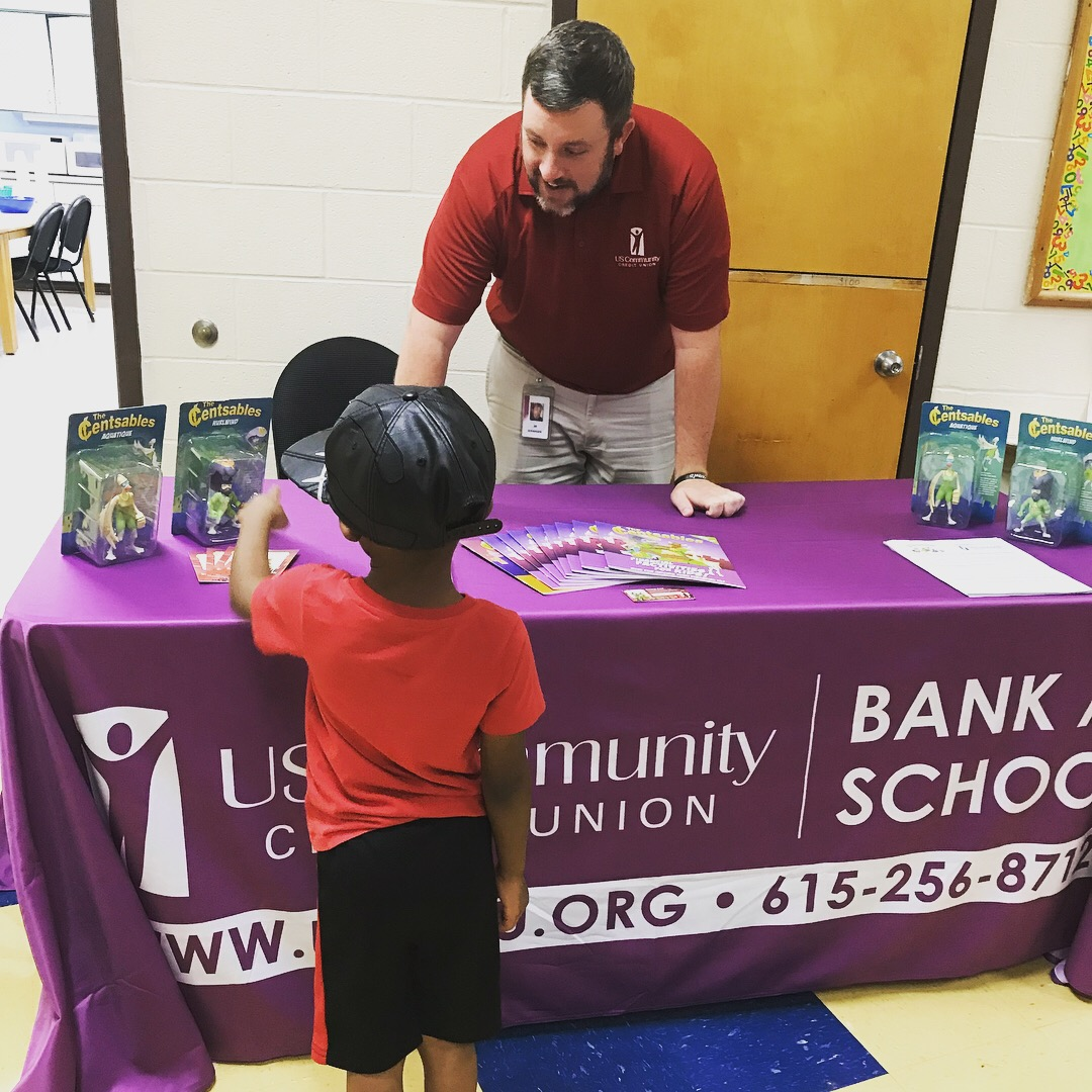 A elementary school student pointing at a Censtables action figure at a USCCU Bank to School table
