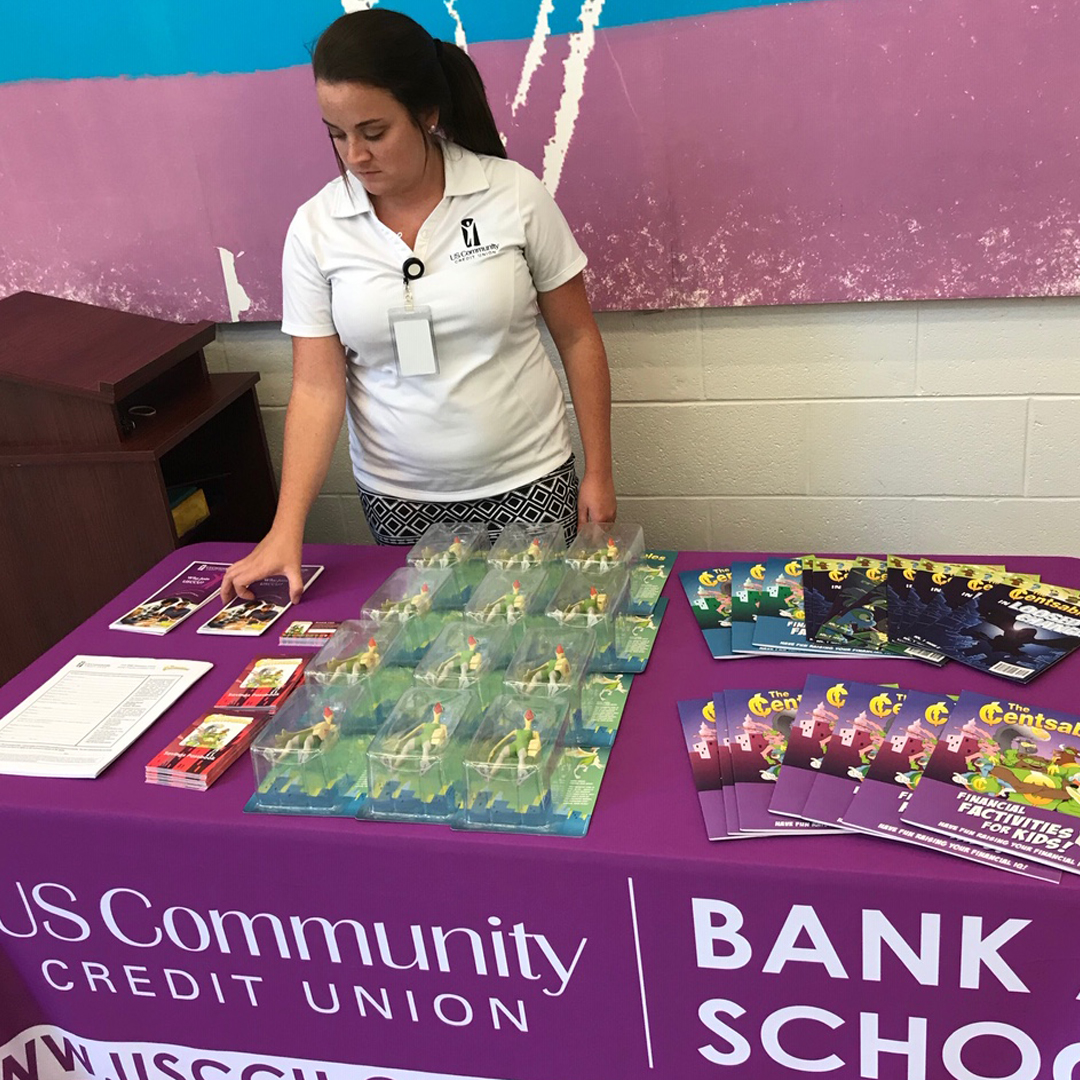 "A USCCU employee arranging Censtables materials on a table with a sign reading ""US Community Credit Union Bank to School"""