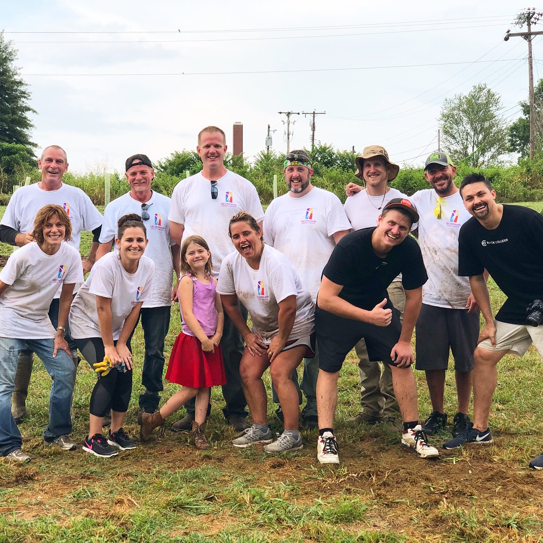Smiling USCCU volunteers cleaning up a field
