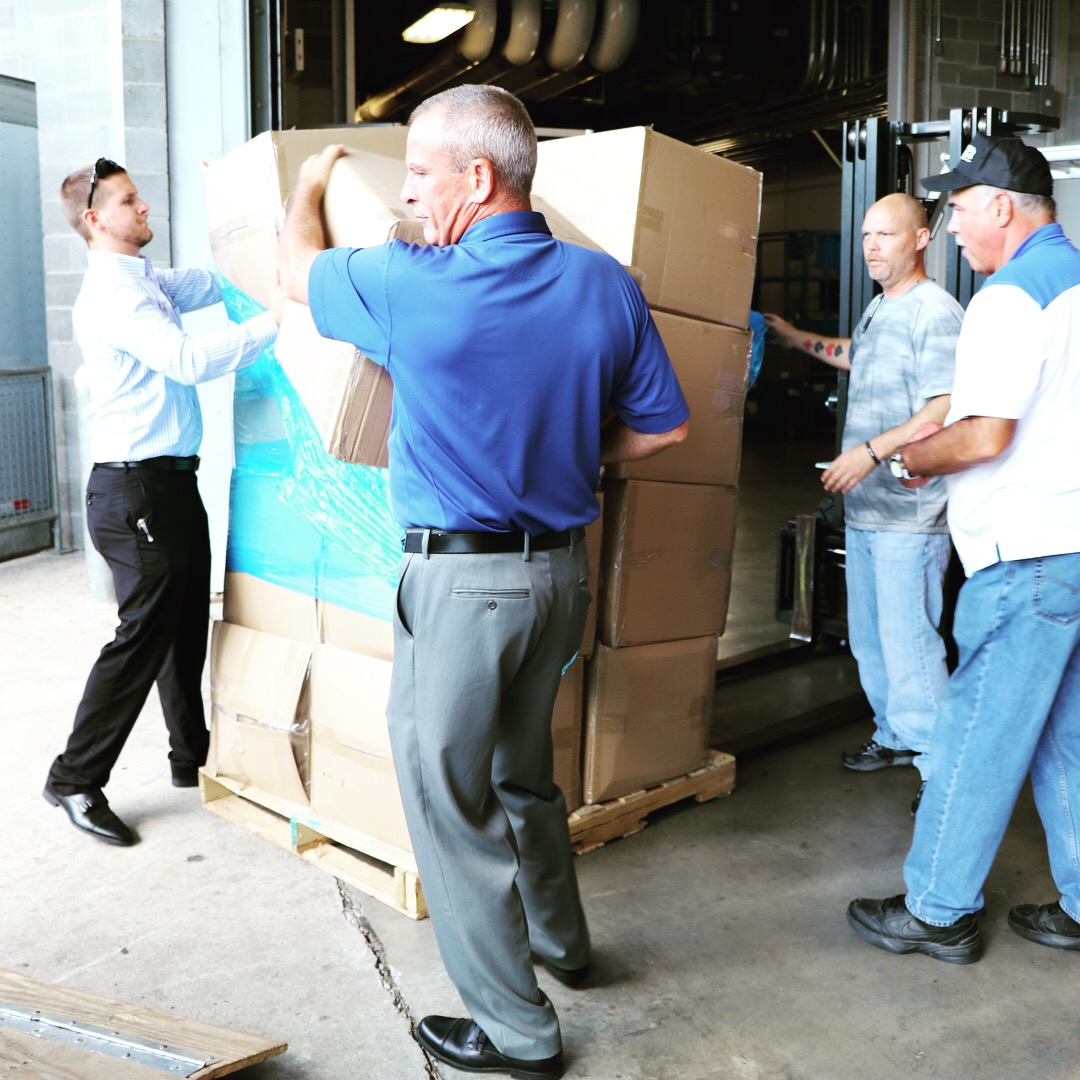 A group of USCCU volunteers helping to move boxes off a palette
