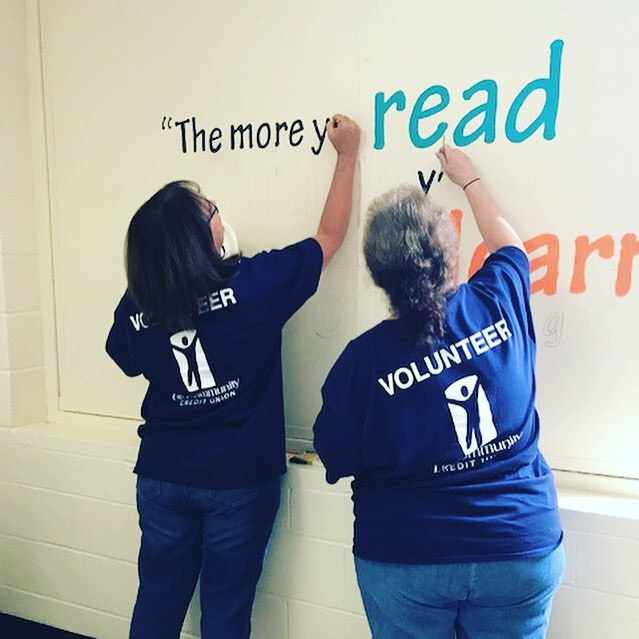 "Two volunteers painting a wall with the words ""The more you read the more you learn"""