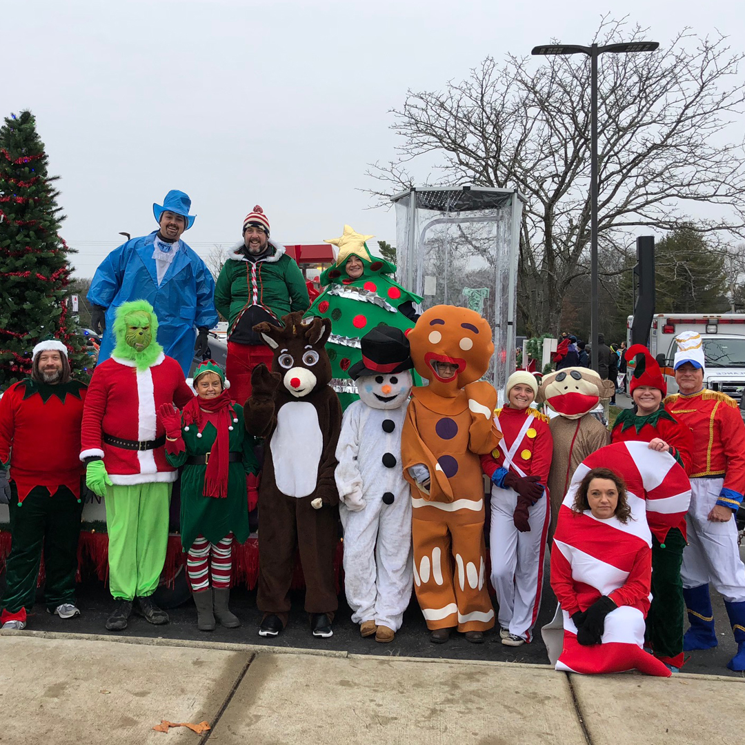 A group photo of USCCU employees dressed as famous Chistmas characters, like the Grinch, Rudolph, Frosty the snowman, and the gingerbread man.