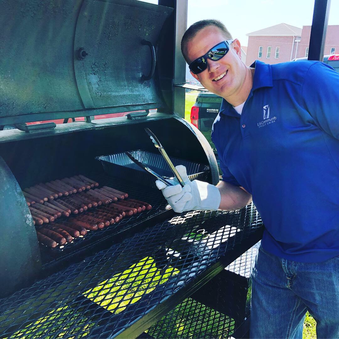 A smiling USCCU employee working the grill at a cookout