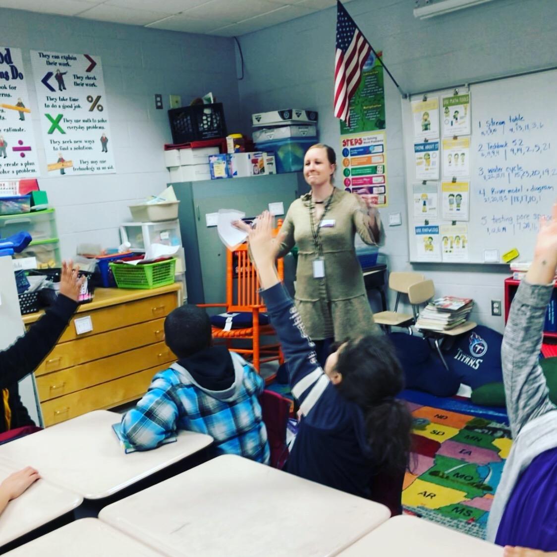 A teacher with a classroom full of children raising their hands